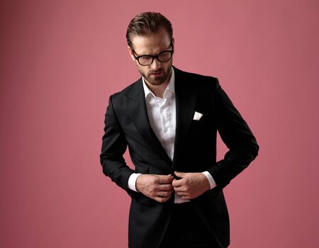 Attractive unbuttoning his jacket while wearing tuxedo and glasses, standing on pink studio background