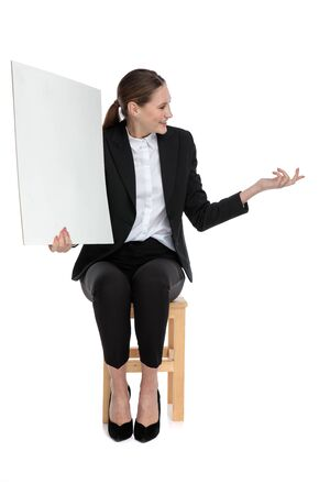 smiling businesswoman wearing black suit sitting and holding a billboard while talking to someone aside against white background