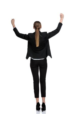 rear view of a businesswoman wearing black suit standing with raised hands and victorious against white studio background