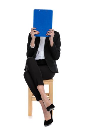shy businesswoman wearing black suit sitting and hiding behind a blue clipboard against white background