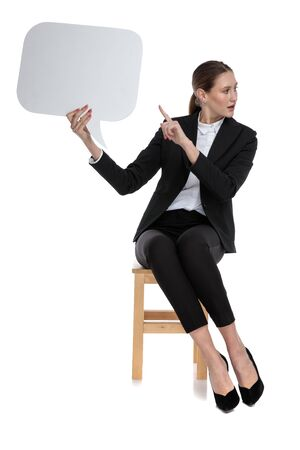 charming businesswoman wearing black suit sitting and pointing to the speech bubble against white studio background
