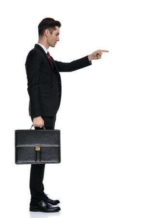 Side view of a confident businessman pointing and holding a briefcase while wearing a black suit and red tie, moving on white studio background