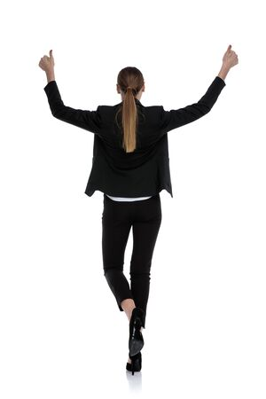 rear view of a businesswoman wearing black suit walking with hands up in the air and thumbs up against white studio background