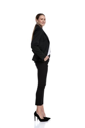 side view of a sexy businesswoman wearing black suit standing and waiting in line with hands in pockets while looking at camera happy against white studio background Stock fotó