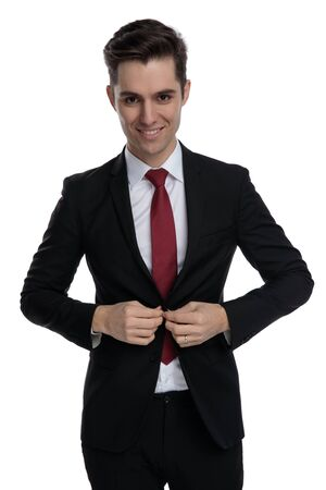Happy businessman unbuttoning his jacket while wearing a black suit and red tie, standing on white studio background 스톡 콘텐츠