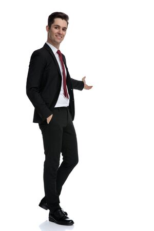 Happy young businessman indicating and holding his hand in his pocket while wearing a black suit and red tie, standing on white studio background Banco de Imagens