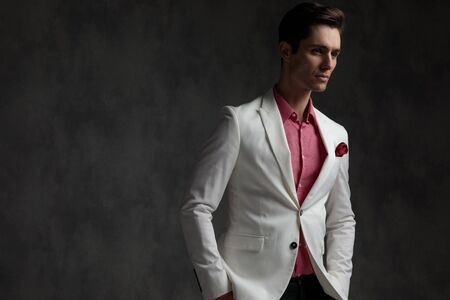 Hopeful elegant man looking away with both hands in his pockets while wearing a white suit and pink shirt, standing, on gray wallpaper studio background
