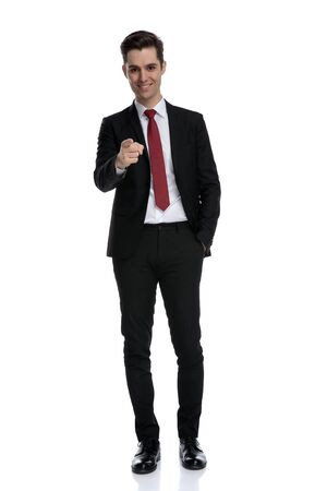 Attractive businessman pointing forward and holding his hand in his pocket while wearing a black suit and red tie, standing on white studio background Banco de Imagens