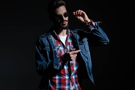 Handsome casual man adjusting pointing and taking off his sunglasses while wearing jeans jacket and a checkered shirt, standing on black studio background Banco de Imagens