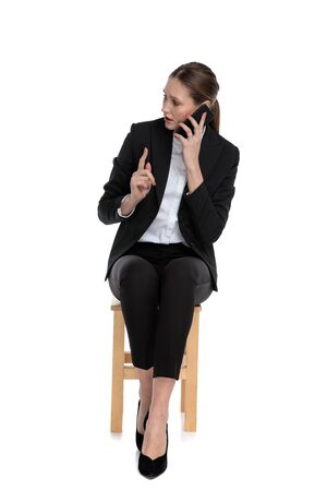 young businesswoman wearing black suit sitting and talking on phone while making a hold on gesture against white studio background