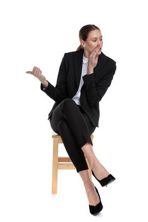jolie femme d'affaires portant un costume noir assise avec les jambes croisées et chuchotant d'un côté tout en pointant l'autre sur fond de studio blanc Banque d'images