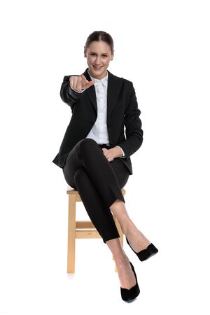 fit businesswoman wearing black suit sitting and pointing forward against white studio background Banco de Imagens