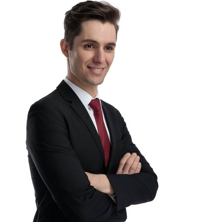 Hopeful businessman holding his arms crossed and wondering while wearing a black suit and red tie, standing on white studio background Banco de Imagens