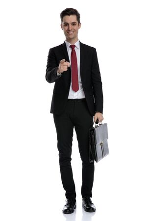 Positive Businessman holding a briefcase adn pointing forward while wearing a black suit and red tie, moving on white studio background Banco de Imagens