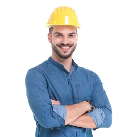 Delighted casual man smiling with his arms crossed at his chest while wearing a construction helmet and blue shirt, standing on white studio background Banco de Imagens