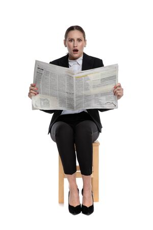 shocked businesswoman wearing black suit sitting and holding the newspaper against white background