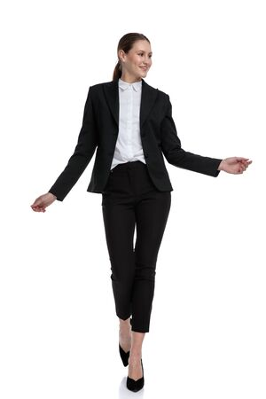 adorable formal businesswoman wearing black suit walking carefreely with loose hands against white studio background Stock Photo