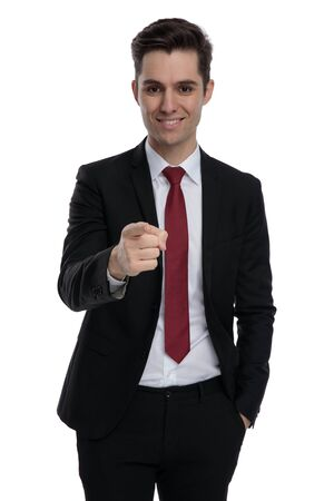 Attractive  businessman pointing forward while wearing a black suit and red tie, standing on white studio background
