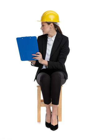 cute businesswoman wearing yellow helmet sitting and pointing to her clipboard against white background