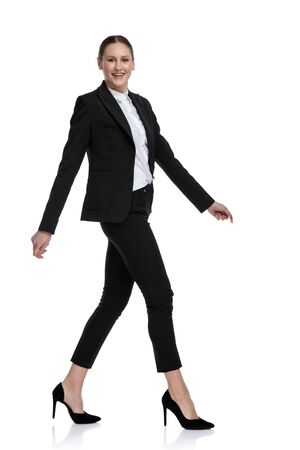 side view of an attractive formal businesswoman wearing black suit walking relaxed and staring at camera happy against white studio background Stock Photo