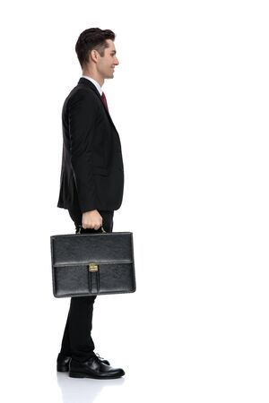Side view of happy businessman looking forward and holding a briefcase while wearing a black suit and red tie, moving on white studio background