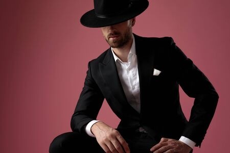 Determined mysterious groom looking away leaning on his leg while wearing tuxedo, a black hat sitting on pink studio background Banque d'images