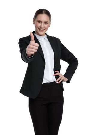 wonderful formal businesswoman wearing black suit standing with hand on hip and ok sign happy against white studio background Stock fotó