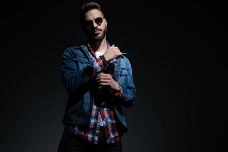 Attractive casual man adjusting his sleeve while wearing sunglasses and a checkered shirt, standing on black studio background