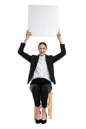 happy businesswoman wearing black suit sitting and holding billboard overhead against white background