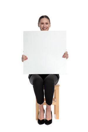 cute businesswoman wearing black suit sitting and presenting a blank billboard against white background
