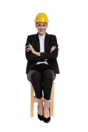 confident businesswoman wearing yellow helmet sitting with crossed arms against white background