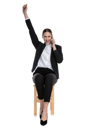 cute businesswoman wearing black suit sitting and talking on phone with one hand up against white studio background