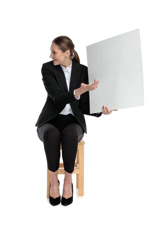 elegant businesswoman wearing black suit sitting and pointing aside to her billboard against white background Stock fotó