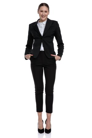 charming formal businesswoman wearing black suit standing with hands in pockets carefree against white studio background Stock fotó