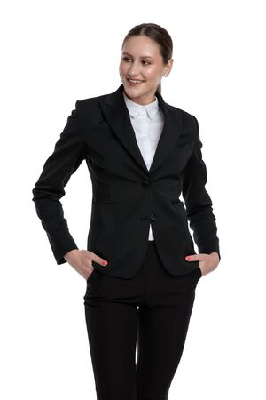 good looking formal businesswoman wearing black suit standing with hands in pockets and looking away relaxed against white studio background Stock fotó