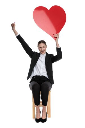happy businesswoman wearing black suit sitting and holding a big red heart overhead and one fist up against white background