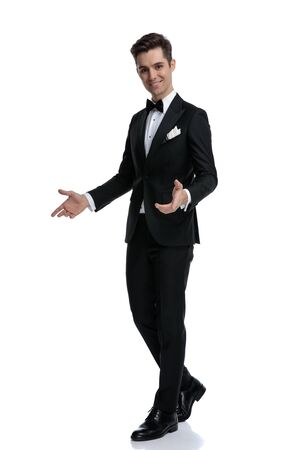 side view of young elegant groom in tuxedo, walking and presenting to side, isolated on white background, full body