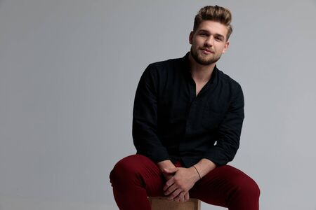 Confident fashion man looking forward and holding his hands together while wearing a black shirt and red jeans, sitting on a box on gray studio background