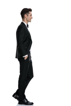 side view of smiling young groom in tuxedo walking isolated on white background in studio, full body