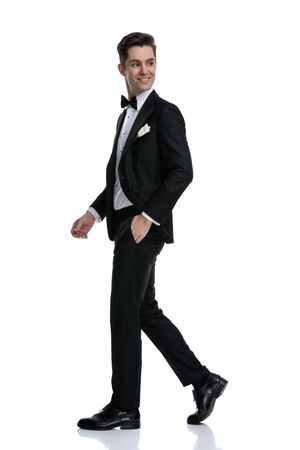 side view of young elegant groom in tuxedo looking to side and walking isolated on white background, full body Stock Photo