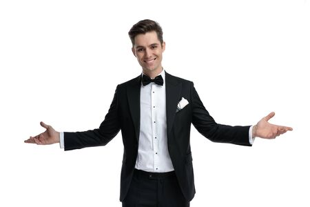 smiling elegant groom in tuxedo opening arms and welcoming, standing isolated on white background