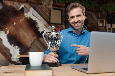 Positive man laughing and pointing to this trophy while wearing a blue shirt, sitting at a desk on coffeeshop background Archivio Fotografico - 133484126