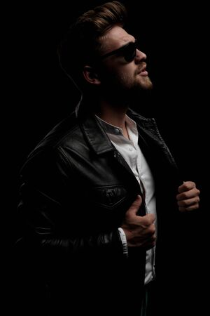side view of a young casual man wearing sunglasses standing and taking off his jacket on black studio background