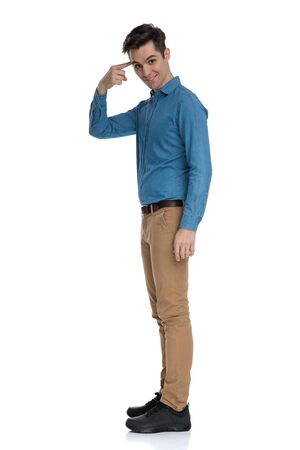 side view of smart casual man pointing finger to head and standing isolated on white background, full body
