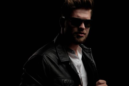close up of a casual man wearing leather jacket standing and pulling his jacket while looking at camera on black studio background