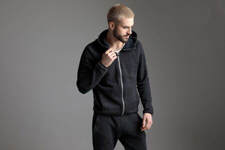 young casual man standing and fixing his tracksuit while looking aside pensive on gray studio background