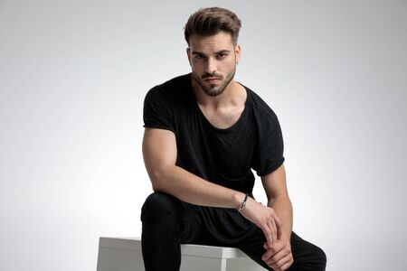dramatic cool guy holding elbow on knee in a fashion pose, sitting on grey background Banco de Imagens