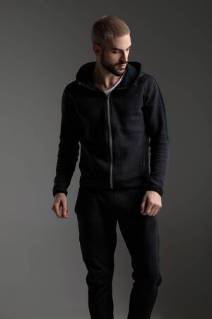 handsome casual man wearing tracksuit standing with loose hands and looking down disappointed on gray studio background Foto de archivo