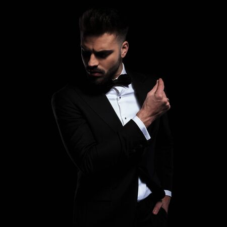 beautiful businessman wearing black tuxedo standing with hand in pocket and clapping fingers while looking down with attitude on black studio background Stock Photo