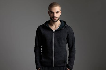 young casual man wearing tracksuit standing with hands in pocket and staring at camera serious on gray studio background Foto de archivo
